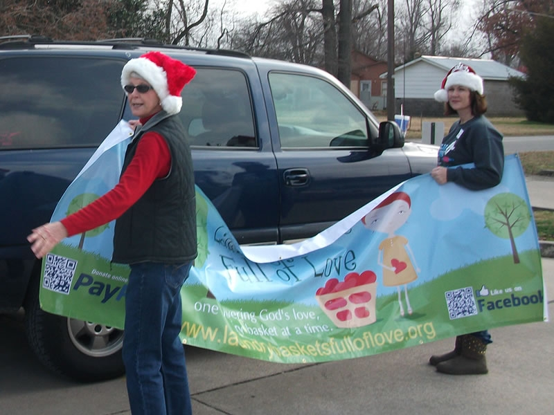 LBFOL volunteers hang our banner in the parking lot