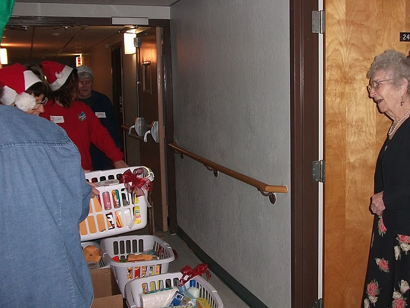 A resident opens her door for a Christmas basket