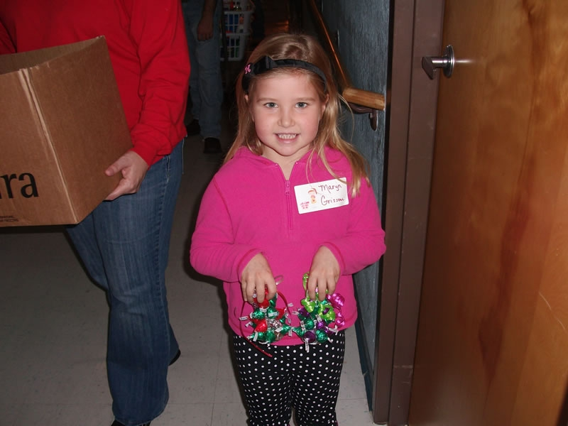 A young volunteer holds some of the Christmas treats to be delivered